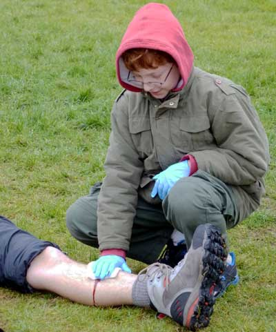 Photo: youth applying direct pressure on bleeding leg during dtWFA class