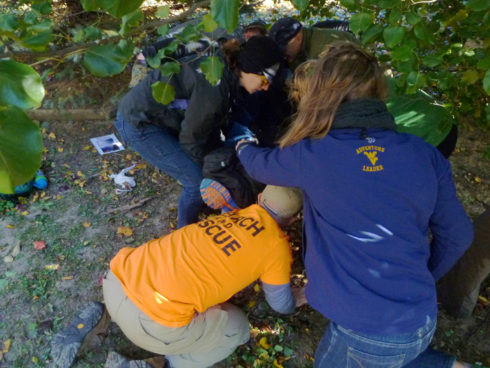Search and Rescue (SAR) find the missing person beneath trees, and prepare to move the patient